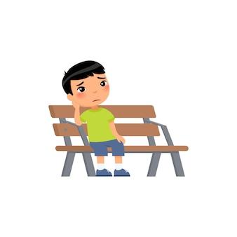 Trauriges kleines asiatisches jungen unglückliches kind, das auf bank sitzt
