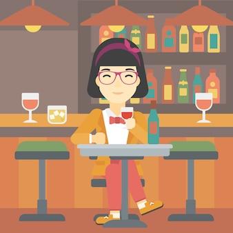 Trinkender wein der frau am restaurant.