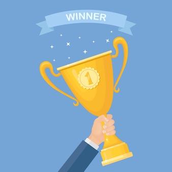 Trophäenbecher in der hand. goldbecher auf blauem hintergrund. auszeichnungen für gewinner, champion. von sieg, auszeichnung, meisterschaft, führung, leistung.