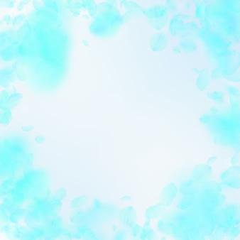 Türkisfarbene blütenblätter fallen herunter. wertvolle romantische blumenvignette. fliegendes blütenblatt auf quadratischem hintergrund des blauen himmels. liebe, romantik-konzept. kreative hochzeitseinladung.