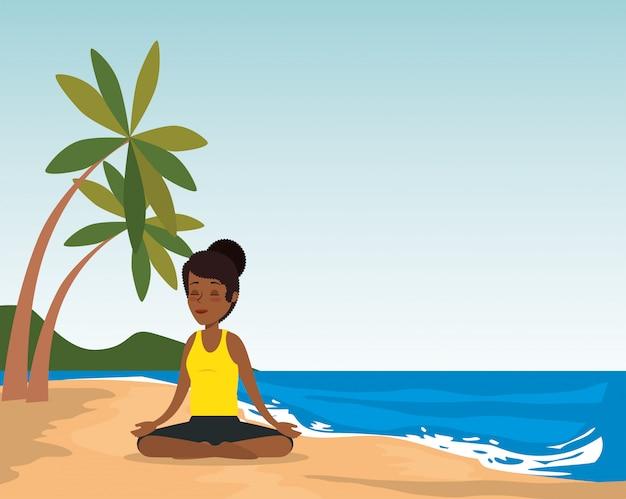 Übendes yoga der schwarzen frau auf dem strand