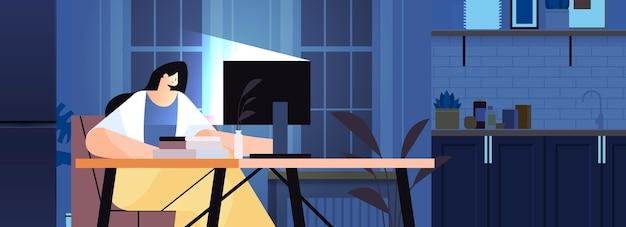 Überarbeitete geschäftsfrau, die am arbeitsplatz sitzt geschäftsfrau-freiberuflerin, die in dunkler nacht das horizontale porträt des heimbüros auf den computerbildschirm schaut