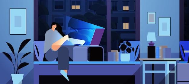 Überarbeitete geschäftsfrau, die auf computerbildschirm schaut, die auf dem bett in dunklem nachtheimzimmer horizontal in voller länge sitzt
