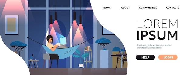 Überarbeitete geschäftsfrau, die auf computerbildschirm schaut mädchen, das in hängematte liegt dunkle nacht zu hause zimmerinnenraum horizontal in voller länge kopienraum