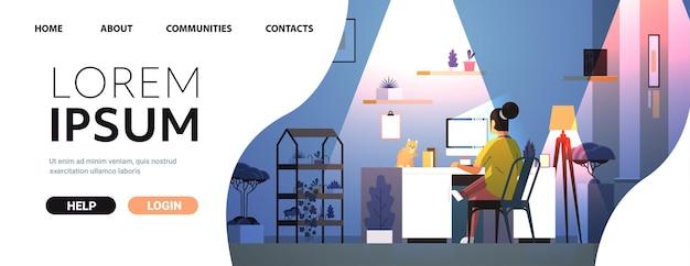 Überarbeitete geschäftsfrau, die auf den computerbildschirm blickt, der am arbeitsplatz mit katze im dunklen nachtwohnzimmer sitzt horizontaler kopienraum in voller länge