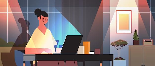Überarbeitete geschäftsfrau, die auf laptop-bildschirm blickt, die am arbeitsplatz in dunklem nachtheimzimmer horizontales porträt sitzt