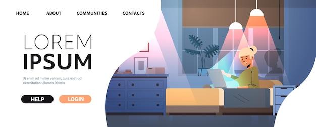 Überarbeitete geschäftsfrau freelancer, die computerbildschirmmädchen ansieht, die auf dem bett in dunklem nachtheimzimmer horizontaler kopienraum in voller länge sitzen