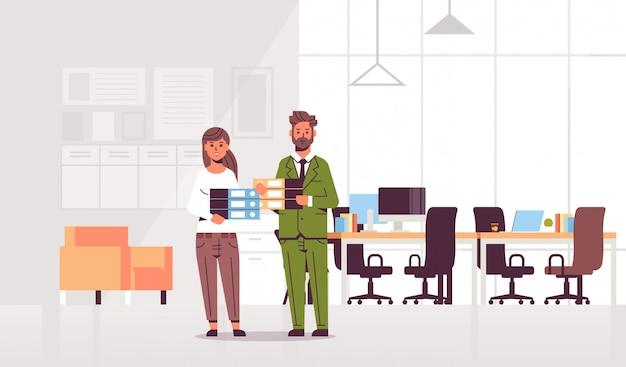 Überarbeitete geschäftsleute mann frau hält ordner stapel paar überladene mitarbeiter stehen zusammen papierkram hart arbeitende moderne büroeinrichtung