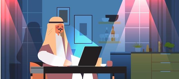 Überarbeiteter arabischer geschäftsmann, freiberufler, der auf laptop-bildschirm schaut arabischer mann, der am arbeitsplatz in dunkler nacht zu hause horizontales porträt sitzt