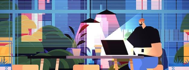 Überarbeiteter geschäftsmann, der am arbeitsplatz sitzt geschäftsmann-freiberufler, der den computerbildschirm in der dunklen nacht des horizontalen porträts des innenministeriums betrachtet