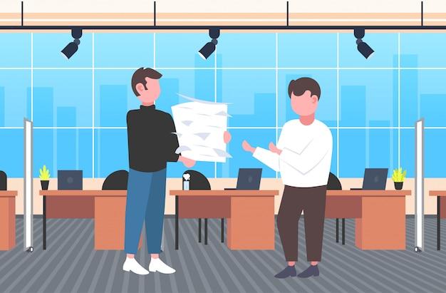 Überarbeiteter geschäftsmann, der papierdokumentenstapel zum cheftermin trägt
