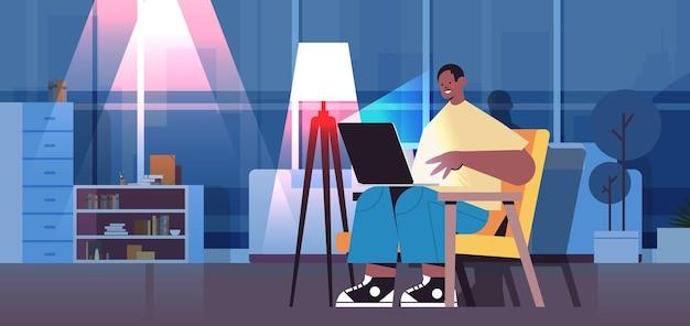Überarbeiteter geschäftsmann, freiberufler, der auf den laptop-bildschirm schaut, der am arbeitsplatz im dunklen nachtheimzimmer horizontal in voller länge sitzt full