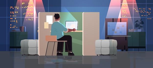 Überarbeiteter geschäftsmann, freiberufler, der auf laptop-bildschirm schaut, der am arbeitsplatz im dunklen nachtbüroraum horizontal in voller länge sitzt