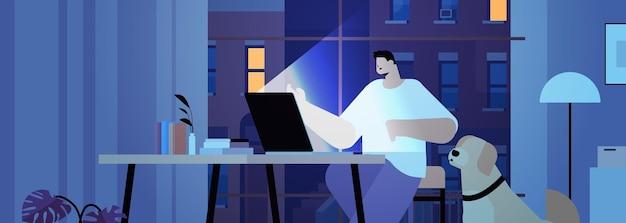 Überarbeiteter geschäftsmann, freiberufler, der auf laptop-bildschirm schaut, der am arbeitsplatz in dunklem nachtheimzimmer horizontales porträt sitzt