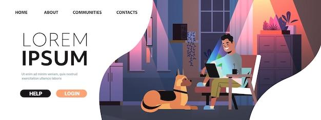 Überarbeiteter geschäftsmann, freiberufler, der einen laptop-bildschirm-mann mit hund ansieht, der in dunkler nacht zu hause arbeitet, horizontaler kopienraum in voller länge
