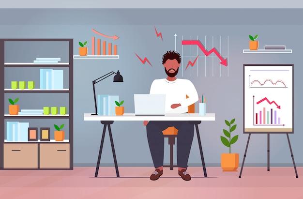Überarbeiteter geschäftsmann unter verwendung des laptops, der den wirtschaftlichen pfeil des abwärtsgraphen analysiert, der den konkurskonzept des modernen büroinnenraums in voller länge horizontal herunterfällt