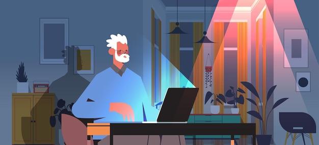 Überarbeiteter senior-freiberufler mit blick auf laptop-bildschirm im alter von mann, der am arbeitsplatz in dunklem nachtheimzimmer horizontales porträt sitzt
