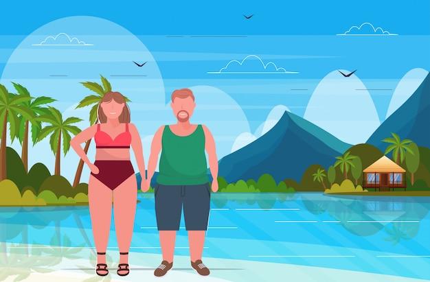 Übergewichtige frau im badeanzug mit mann plus größe paar, das zusammen sommerferienkonzept tropische insel-seestückhintergrund in voller länge flach horizontal steht