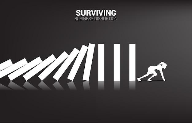 Überleben von geschäftsstörungen. silhouette der geschäftsfrau, die bereit ist, vom domino-zusammenbruch wegzulaufen. konzept der unternehmensbranche stören