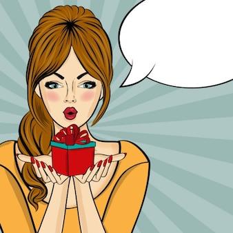 Überrascht pop-art-frau, die mit sprechblase pin up mädchen, das ein geschenk in ihren händen comic frau hält