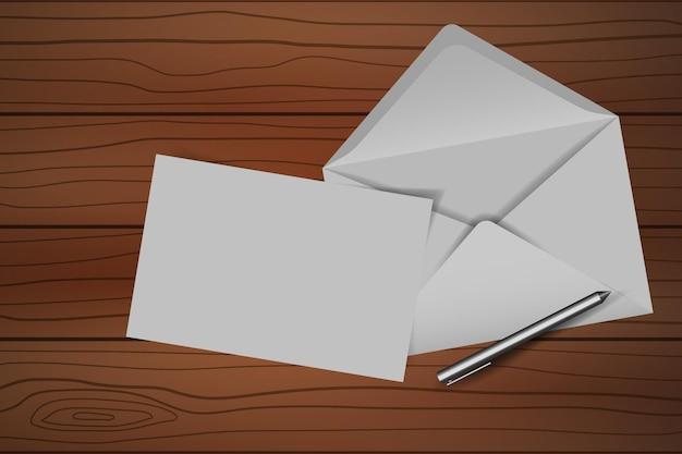 Umschlag mit leerer notiz und stift auf holztisch