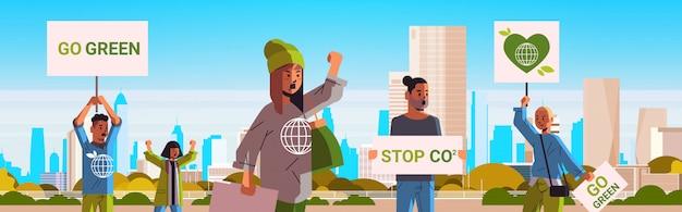 Umweltaktivisten, die plakate halten, werden grün, retten demonstranten des planetenstreikkonzepts, die sich für den schutz der erde einsetzen und gegen die horizontale erwärmung des porträt-stadtbildhintergrunds horizontal demonstrieren