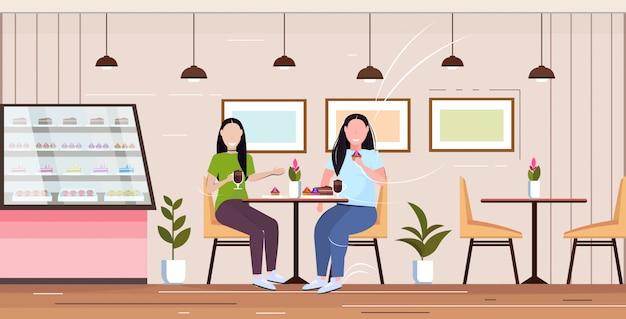 Und dünne mädchen sitzen am tisch und essen süße kuchen ungesunde ernährung fettleibigkeit konzept frauen paar verbringen zeit zusammen moderne café interieur in voller länge horizontal