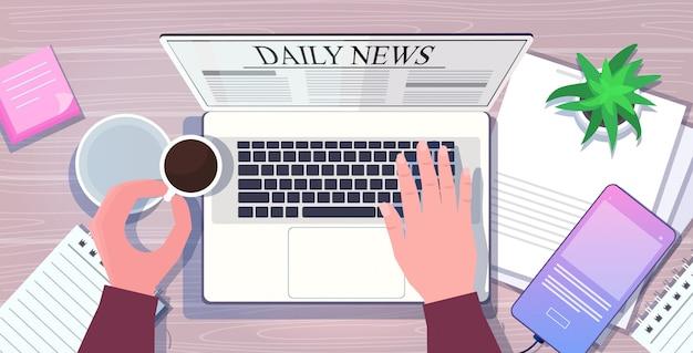 Unternehmer, der tägliche nachrichtenartikel auf laptop-bildschirm liest online-zeitungspresse massenmedienkonzept. horizontale darstellung der arbeitsplatz-tischwinkelansicht