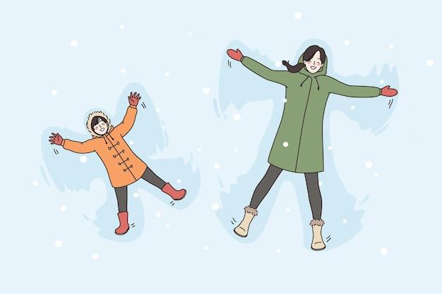Urlaub winteraktivitäten freizeitkonzept. glückliches lächelndes frauen- und kinderpaar, das im winter zusammen vektorillustration liegt und schneeengel spielt