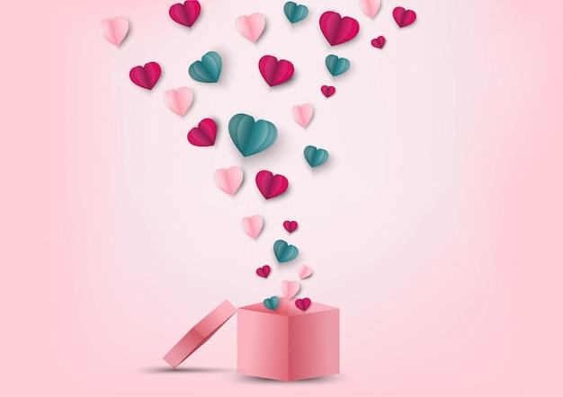 Valentinsgrußherzen und geschenkbox. origami machte das papierherz, das heraus weg von der geschenkbox fliegt