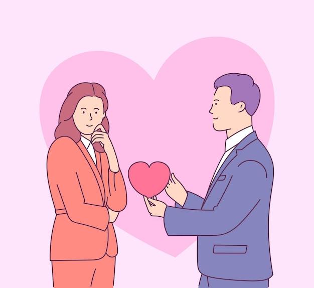 Valentinstag mit verliebtem jungem paar. junger mann gibt herzförmige karte zur lächelnden frau.