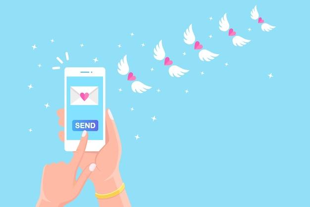 Valentinstag . senden oder empfangen sie liebes-sms, briefe, e-mails mit dem handy. weißes handy in der hand auf hintergrund. fliegender umschlag mit rotem herzen, flügeln.