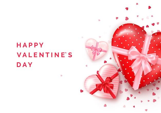 Valentinstagsgruß. herzförmige geschenkboxen mit seidenschleife und konfetti