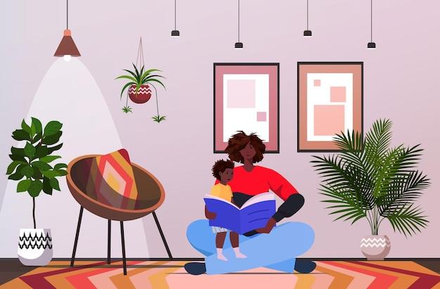 Vater liest buch mit kleinen sohn eltern vaterschaftskonzept vater verbringt zeit mit seinem kind zu hause horizontal in voller länge