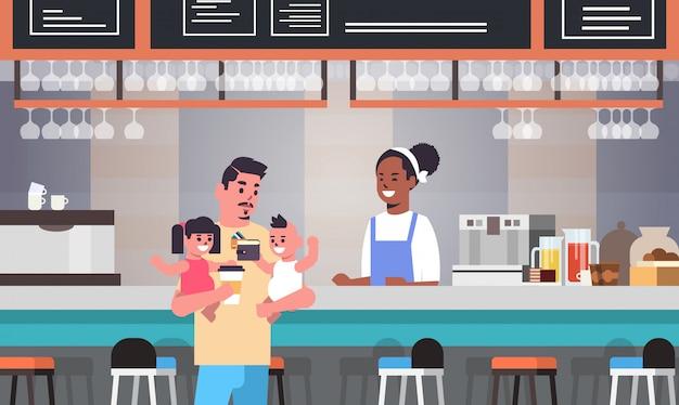 Vater mit kleinem sohn und tochter am kaffeeschalter, der für kaffee bezahlt vaterschaftskonzept glückliche familie, die spaß moderne cafeteria interieur hat
