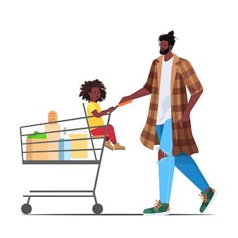 Vater mit kleiner tochter im einkaufswagen, der lebensmittel im supermarktvaterschafts-elternschaftseinkaufskonzept kauft