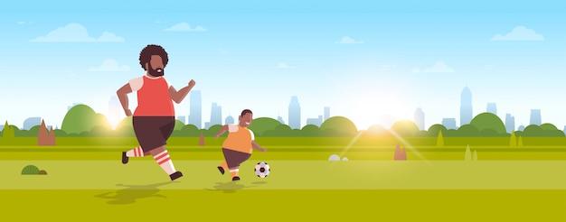 Vater mit sohn, die fußballfamilie spielen, die spaß auf grünem rasen am parkaktivitätskonzept horizontal spielt