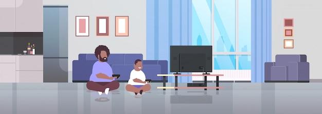 Vater mit sohn hält joystick game pad familie, die videospiele auf dem fernsehbildschirm ungesunden lebensstil ausübt