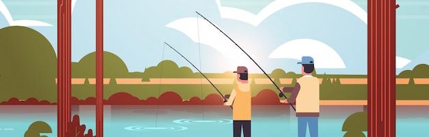 Vater und sohn fischen zusammen rückansicht mann mit kleinem jungen unter verwendung von stangen glückliches familienwochenende fischer hobby konzept sonnenuntergang berge landschaft porträt