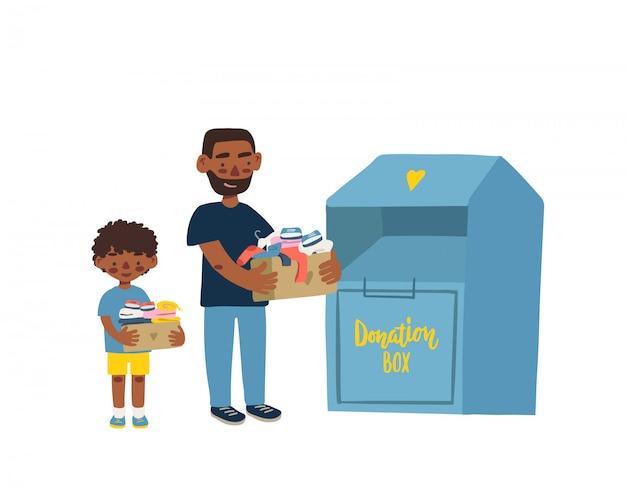 Vater und sohn halten pappkartons mit kleidung zum spenden oder recycling und kleidungsbehälter.