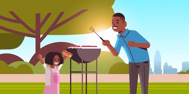 Vater und tochter bereiten hot dogs auf grill glückliche afroamerikanerfamilie vor, die spaßpicknickgrillpartykonzept sommerparklandschaftshintergrund flaches porträt horizontal hat