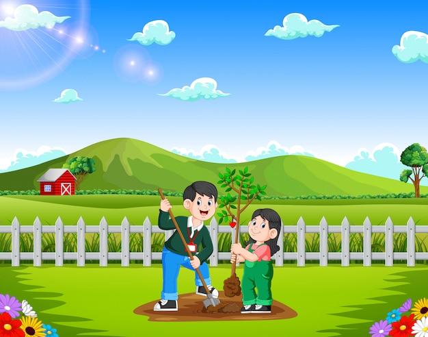 Vater und tochter, die baum im park pflanzen