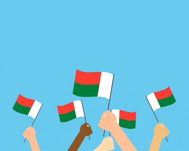 Vector illustration von den händen, die madagaskar-flaggen halten