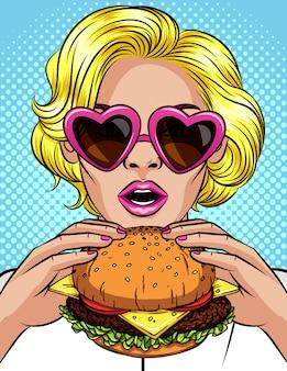 Vector komische artillustration der farbpop-art eines mädchens, das einen cheeseburger isst. schöne geschäftsfrau, die einen großen hamburger hält. erfolgreiche junge dame mit offenem mund beißt einen riesigen burger