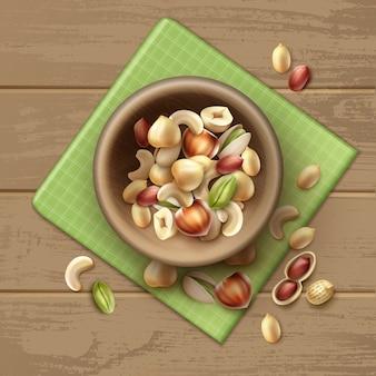 Vektormischung von verschiedenen nüssen in holzschale ganze und halbe haselnuss, pistazie, erdnüsse, cashew auf tisch mit grüner karierter serviette