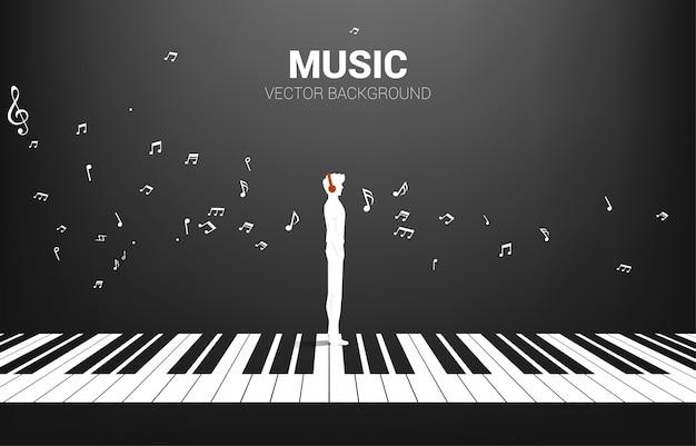 Vektorsilhouette des mannes, der mit klavierschlüssel mit fliegender musiknote steht. konzept hintergrund klaviermusik und erholung.