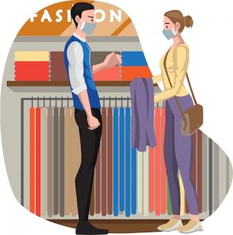 Verkäufer, der einen käufer bedient, der kleidung im modegeschäft kaufen möchte