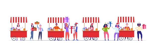 Verkäufer in santa hat, die geschenkboxen verkaufen, mischen rassenleute, die einkaufen und geschenke auf dem weihnachtsmarkt oder in den schönen winterferien kaufen