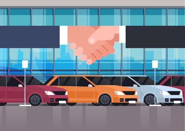 Verkäufer-mann-hand, die mit inhaber über fahrzeug-ausstellungsraum-innenauto-kauf-verkauf oder mietkonzept rüttelt