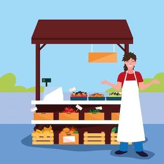 Verkäufer mit stallkiosk des speichergemüses und -obsts